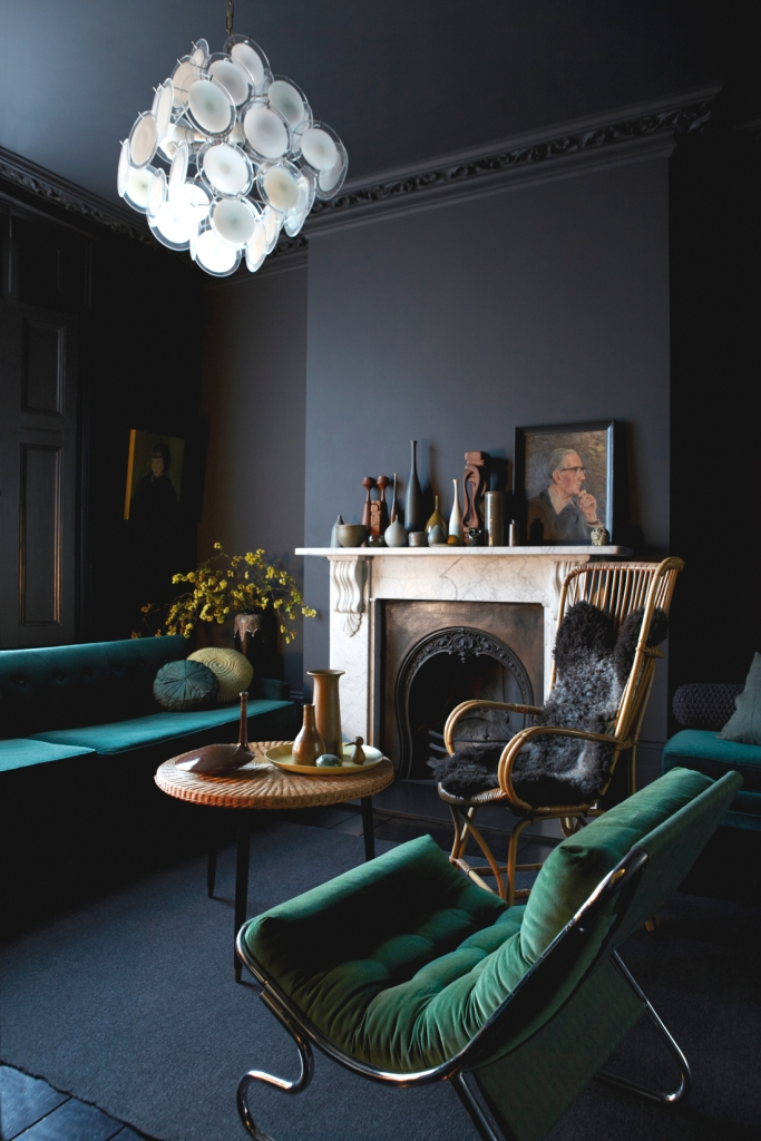 La chimenea de mármol y la lámpara forman el foco de atención del espacio al ser elementos claros en un entorno oscuro.
