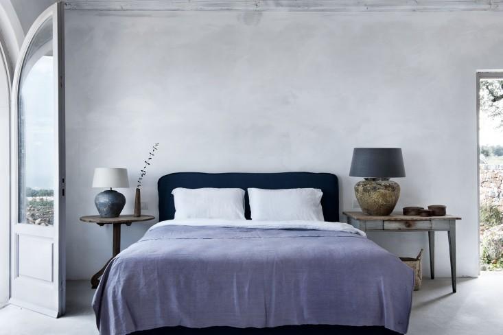 Vista general del dormitorio, con el cabecero tapizado y las lámparas simétricas.