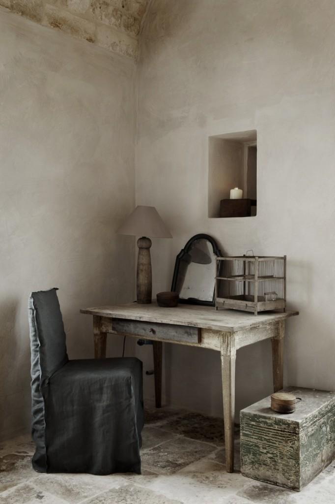 Precioso rincón en tonos tierra, con un escritorio antiguo y su lámpara.