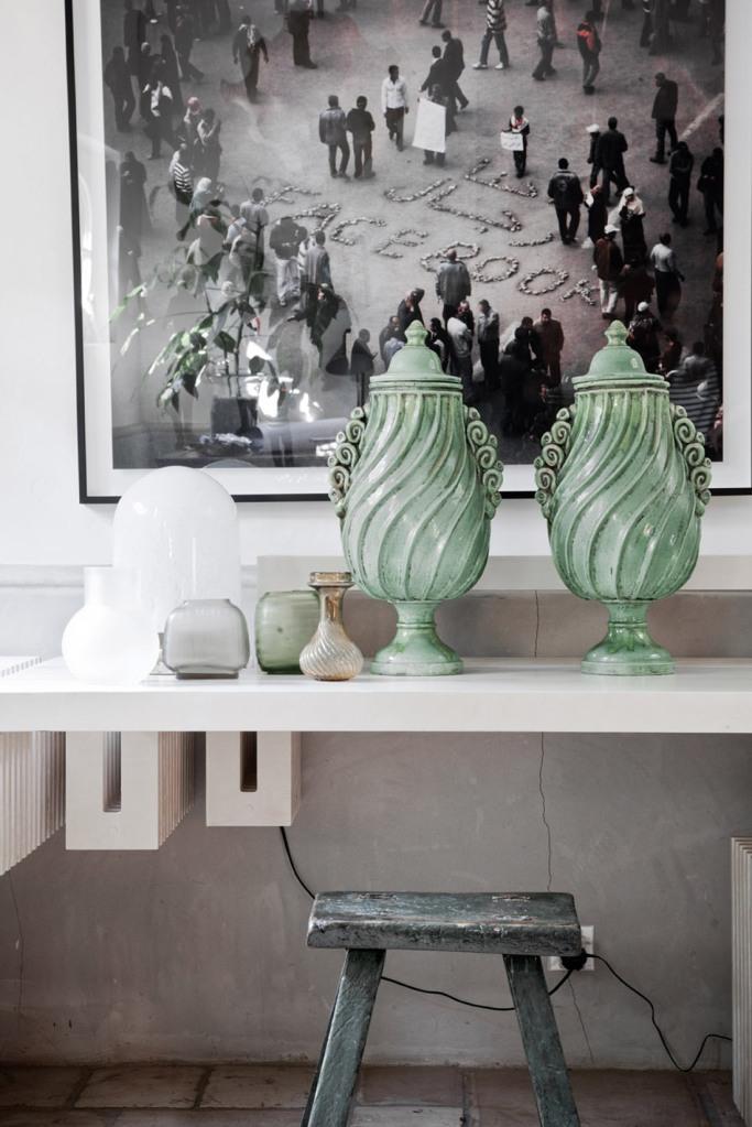Un rincón decorado de manera sobria con una foto muy actual en blanco y negro y los jarrones verdes aguamarina.
