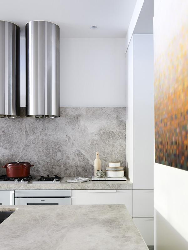 El cuadro de la derecha aporta color a este espacio de cocina muy neutro. La veta del mármol es otro elemento decorativo.