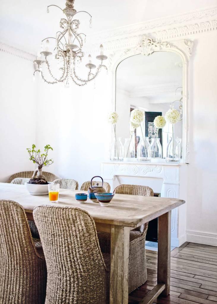 En el comedor destaca la presencia de la hermosa chimenea y la combinación de las sillas de ratán o mimbre, la mesa de madera desgastada y la lámpara de lágrimas o chandelier.