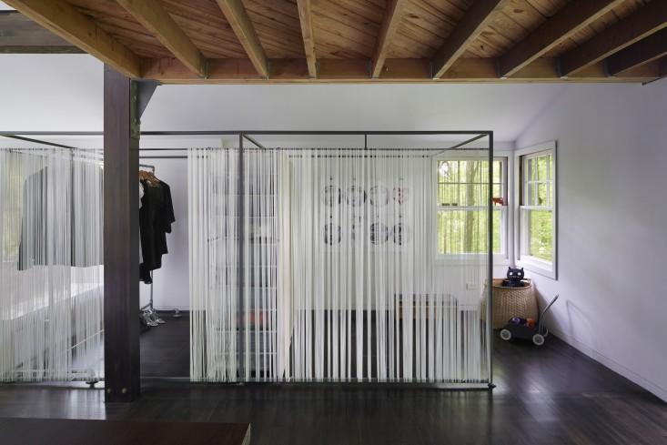 Cierre de estructura de  hierro y cortinas de cuerda que esconde la habitación infantil y el vestidor.