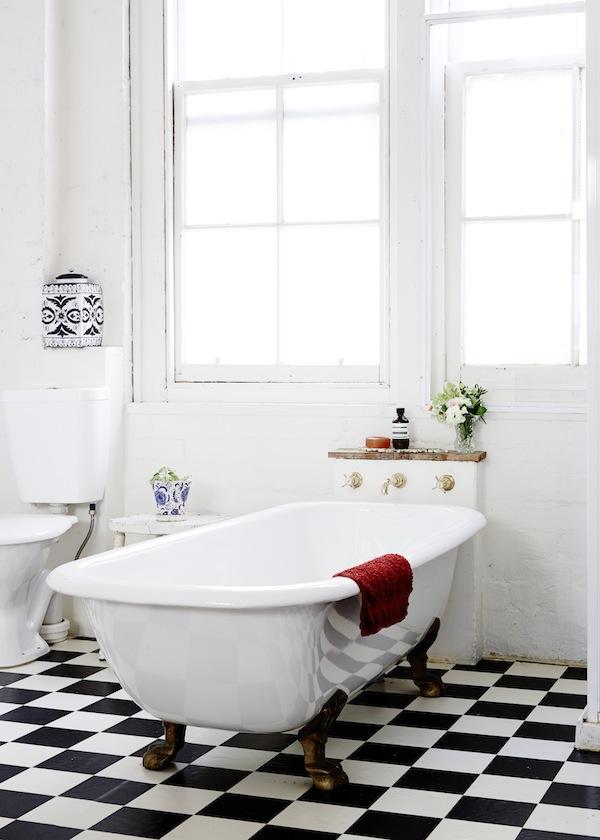 El baño mantiene el estilo industrial y clásico, con el pavimento en damero blanco y negro y las ventanas muy industriales.