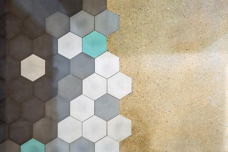 Encuentro del pavimento continuo al cerámico hexagonal. Los colores utilizados son azul, presente en las paredes, el gris y blanco, colores neutros, en diferentes proporciones.