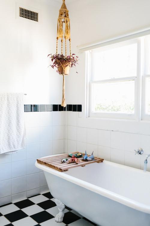 El baño, muy sencillo está alicatado de blanco y el suelo con damero negro y blanco. La bañera de patas le da un toque muy vintage.