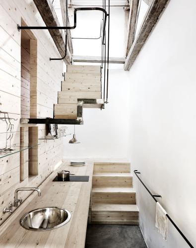 La cocina está en una zona de paso, de subida y de bajada, aprovechando uno de los costados que tiene luz natural en el almacén.