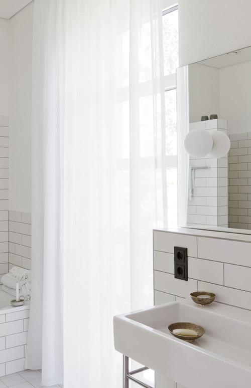Las baldosas blancas rectangulares del baño, la junta negra y los apliques de globo dan a este baño un aire retro precioso.