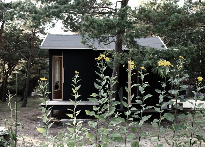 La cabaña está pintada de negro en su exterior y se mezcla muy bien con los colores del bosque.