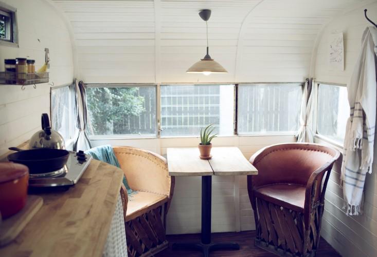 Zona de comedor, con una lámpara colgante , butacas de piel y mesa lacada blanca.