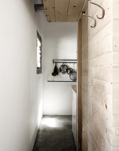 Paso a la cocina, hecha del mismo material. El suelo es un cemento pulido y las paredes parecen encaladas blancas.