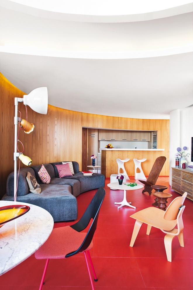 Vista de la cocina integrada en el salón, por medio del empanelado de madera que recorre toda la vivienda. El suelo y los colores son los propios del resto del edificio, parece que se hubiera ajustado a lo que el edificio tenía.