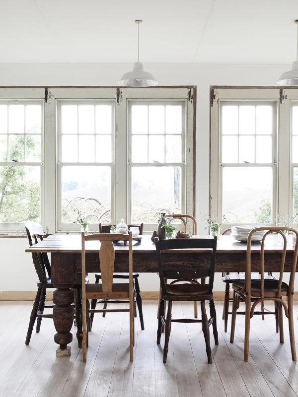 Vista del comedor formal. Las sillas diferentes, los ventananles con luz y las paredes blancas hacen de este lugar lunimoso un perfecto rincón muy acogedor.