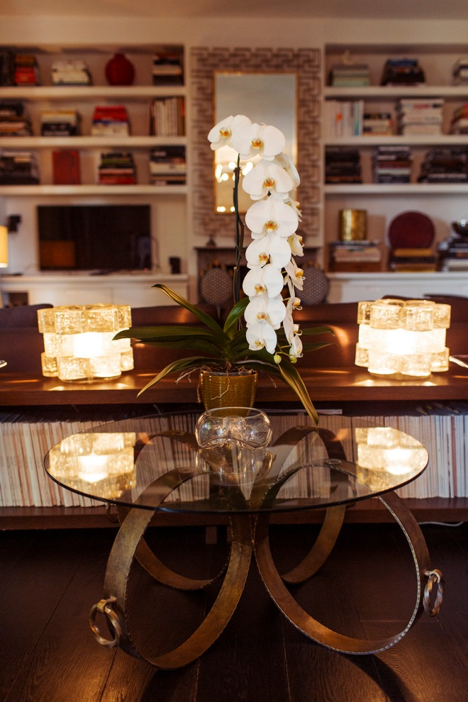Mesa con estructura dorada y con sobre de vidrio. La composición decorativa es simétrica, algo que siempre queda bien.