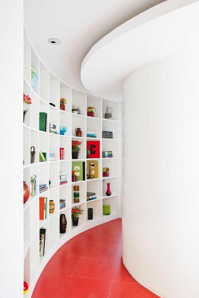 El pasillo curvo con librería genera una sensación de continuidad de los espacios.