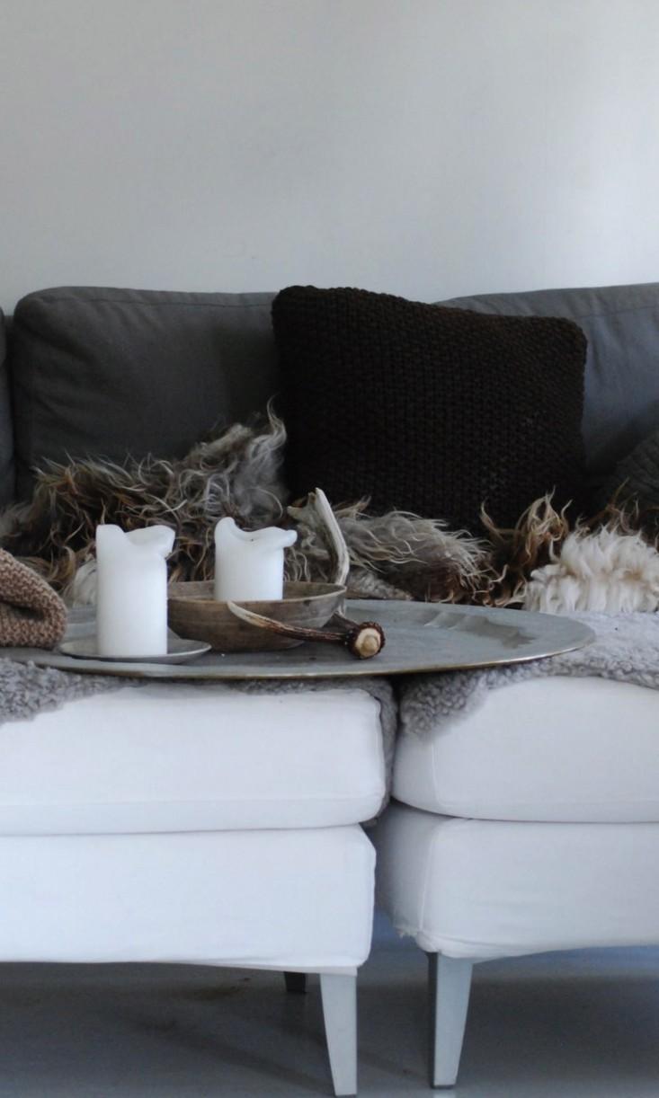 La zona del salón con mantas, velas y cornamentas, elemento muy utilizado en la decoración nórdica. Los animales mudan la cornamenta y es habitual encontrarse con los restos en los bosques.