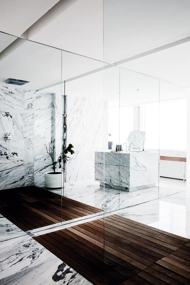 En el baño han creado un espacio muy  sugerente, donde los límite se pierden, fresco,  agradable, por el uso de materiales naturales,como el mármol y la madera.