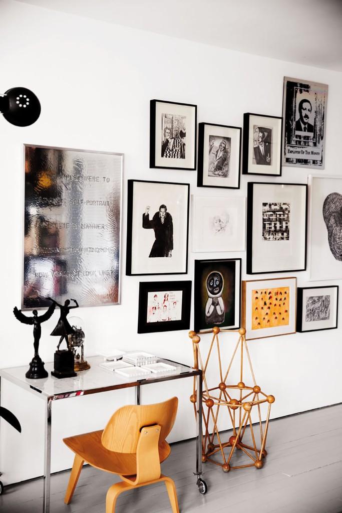 El pequeño rincón de trabajo se  forma por una mesa sencilla,una silla de madera de la serie Plywood de los Eames y una composición de fotos y grabados que casan perfectamente con el resto de elementos. Esta composición de cuadros es la transición entre el espacio de trabajo y el comedor.