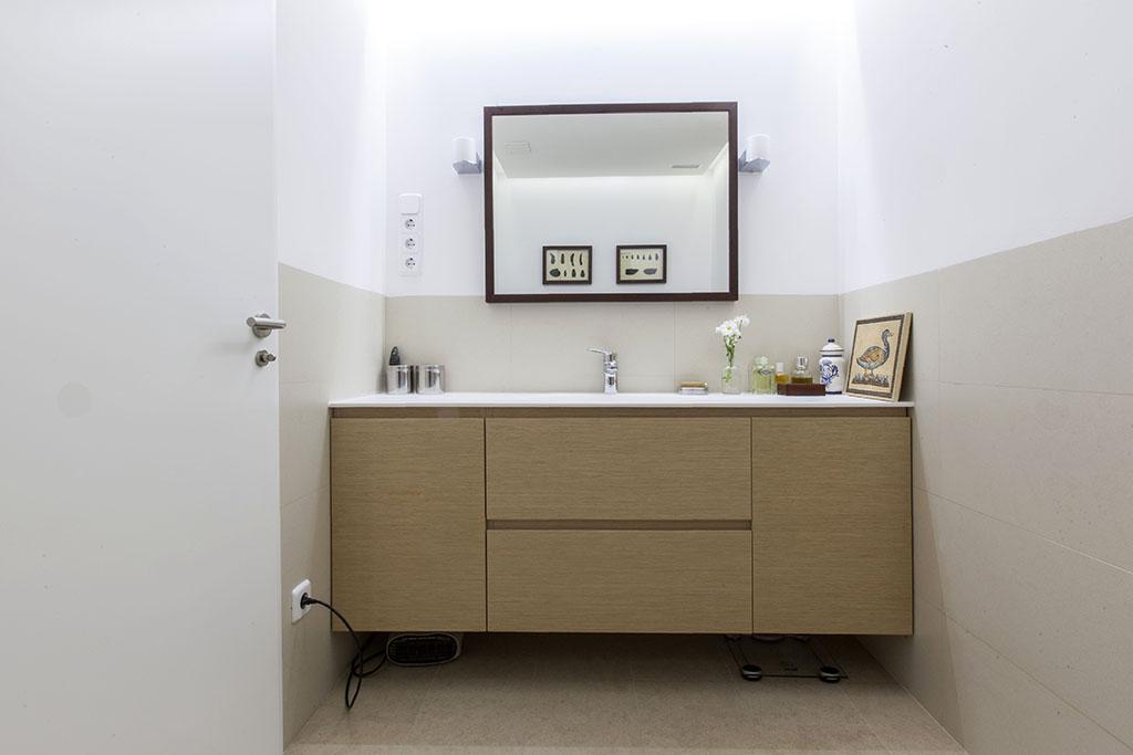Frontal del baño con espejo y cuadros. Los azulejos de este baño son de Porcelanosa.